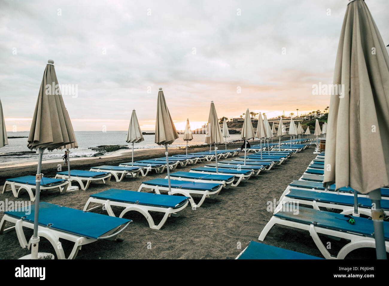 umbrellas and seats in closed business at the beach after a day full of sun and vacation outdoor leisure concept. colors and relaxed time in sunset sk - Stock Image
