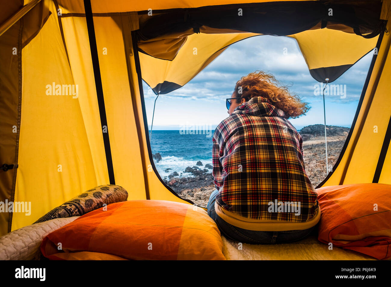 nice woman view from backside sitting outside of a tent mounted on a car. outdoor freedom vacation alternative concept looking ocean out of the door.  - Stock Image