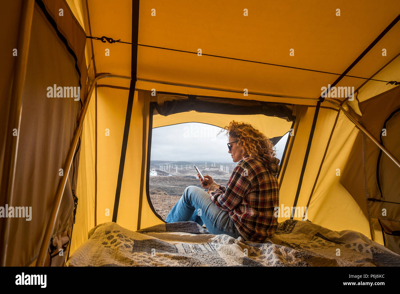 beautiful caucasian woman check the smartphone for internet contacts and work while sit down outside a tent with ocean view. travel and work concept w - Stock Image