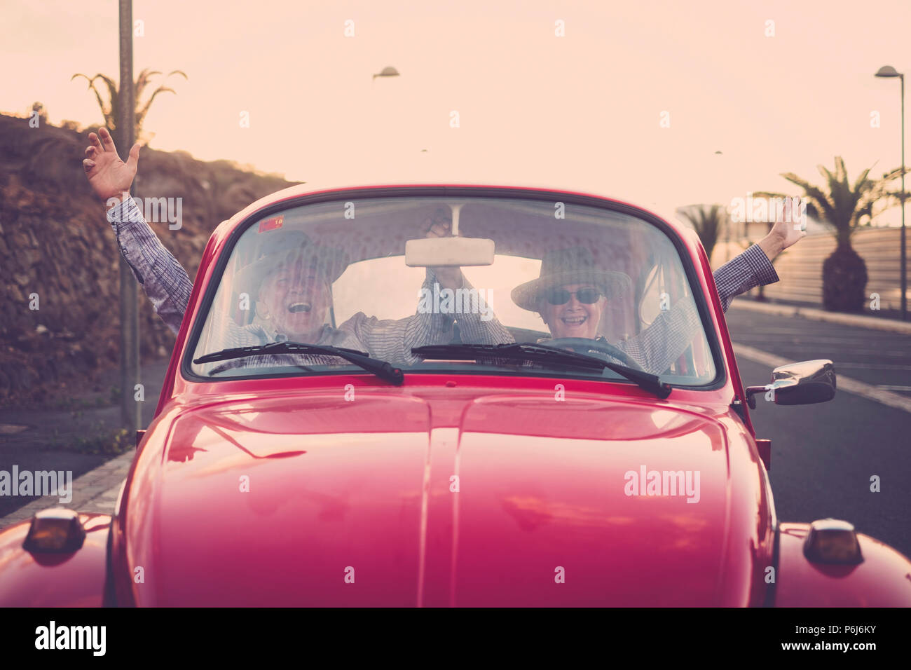 senior adult couple crazy drive with no hands in funny leisure activity. travel happy concept for retired lifestyle and couple in love. shout and laug - Stock Image