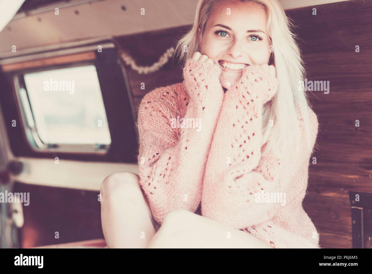 Beautiful blonde model white caucasian skin with beauty face smile at you looking at the camera. sit down in a van with wood interior ready to travel  - Stock Image