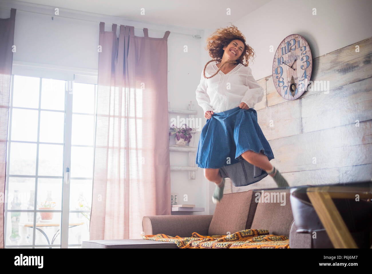 lonely crazy beautiful woman middle age jumping at home for satisfaction or victory. smile a lot and have funwith a big jump on the sofa. freedom and  - Stock Image