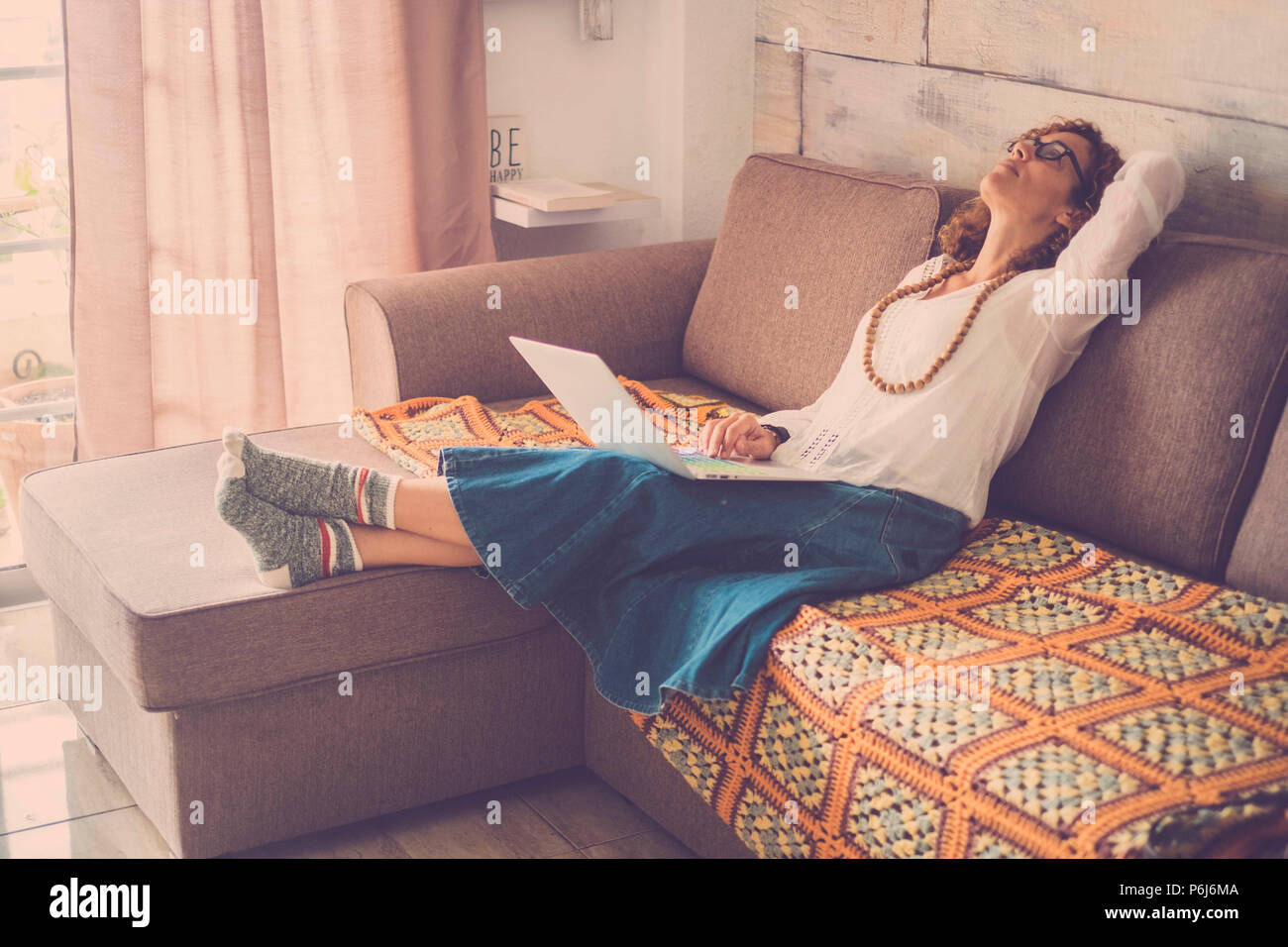 stressed out beautiful middle age woman working at laptop on the sofa at home. internet alternative office for online digital worker. tired looking on - Stock Image
