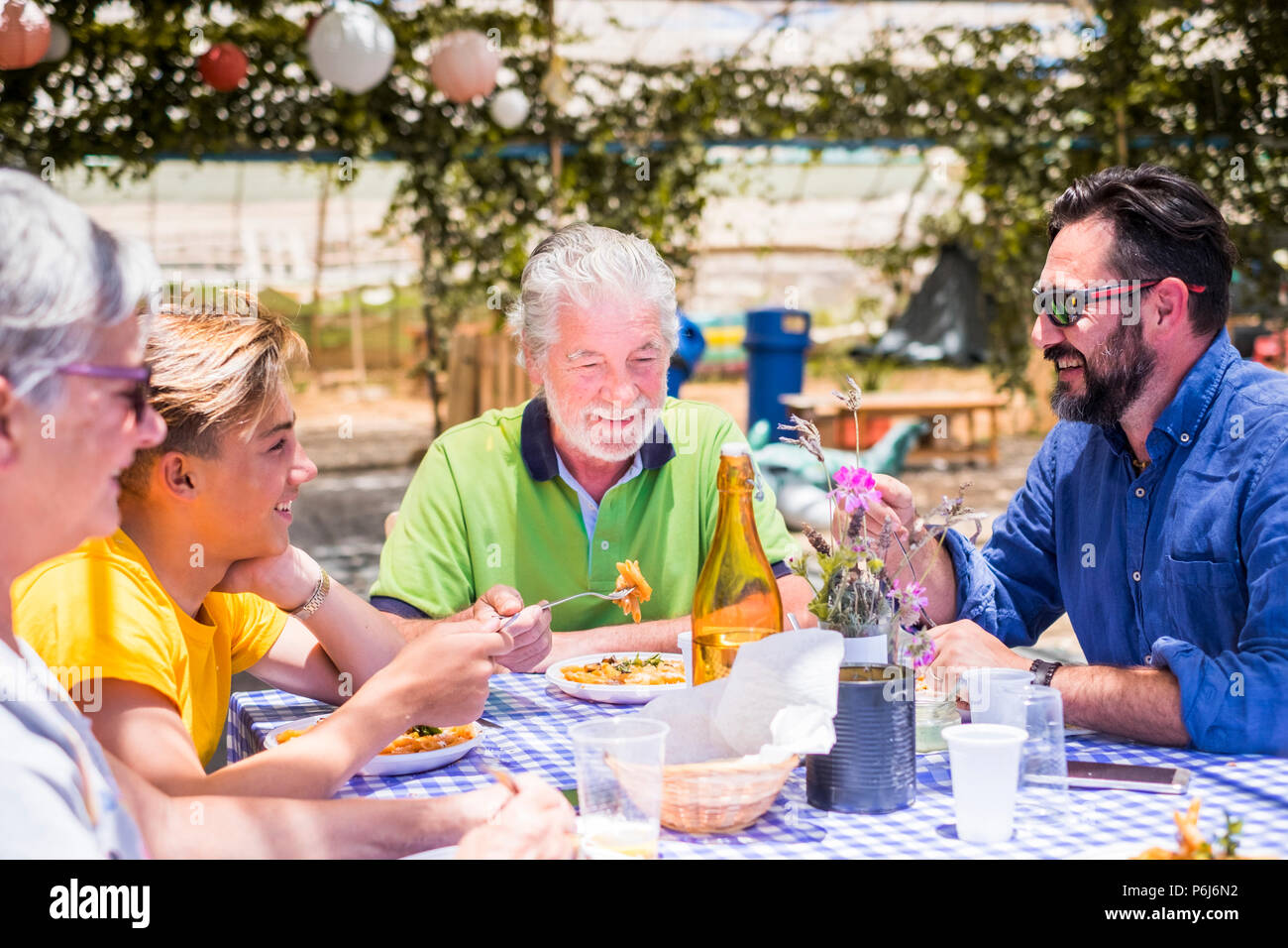 happy family eating together in outdoor restaurant. colors and happiness for cacuasian young and old people. son, father, grandfathers enjoy leisure a - Stock Image