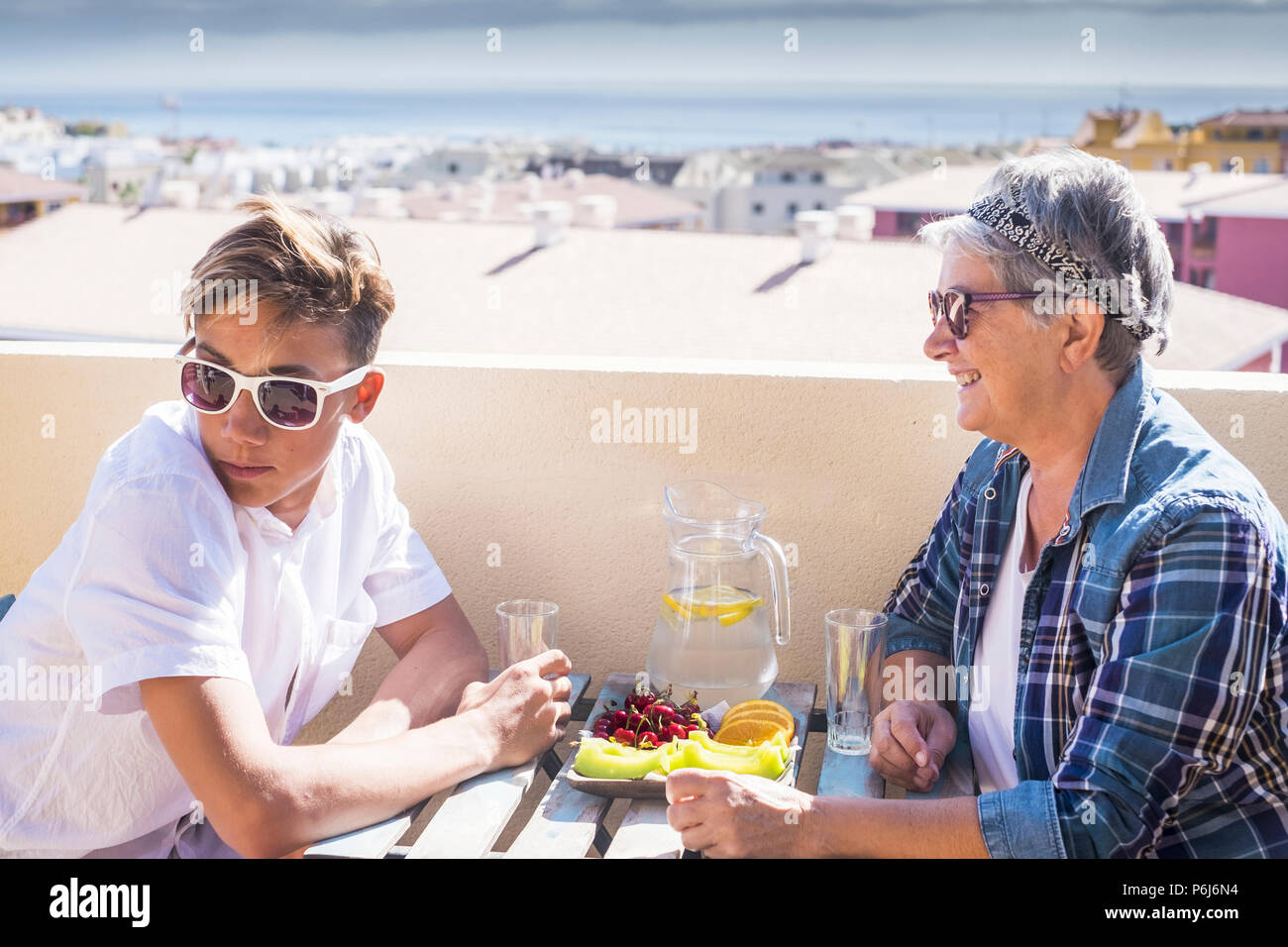 Happy and smiled couple teenager boy and grandmother female. beautiful people outdoor having breakfast in the morning on a terrace with ocean and buil - Stock Image