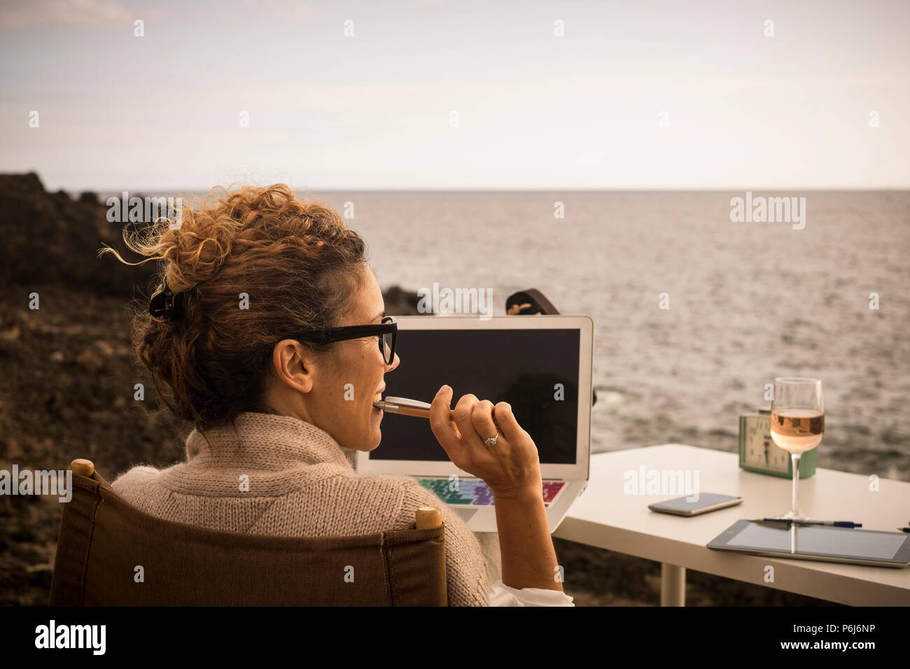 Nice lifestyla for nbeautiful caucasian woman working in alternative office place. outdoor in front of the ocean. digital nomad and internet work for  - Stock Image