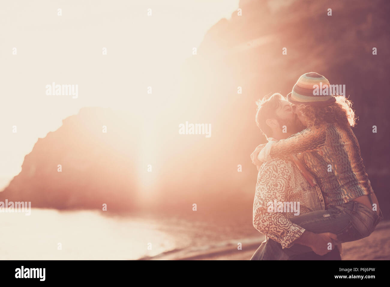 middle age caucasian couple kissing on the beach during an amazing golden warm sunset with ornage and red colors. hugging and carrying with passion an - Stock Image