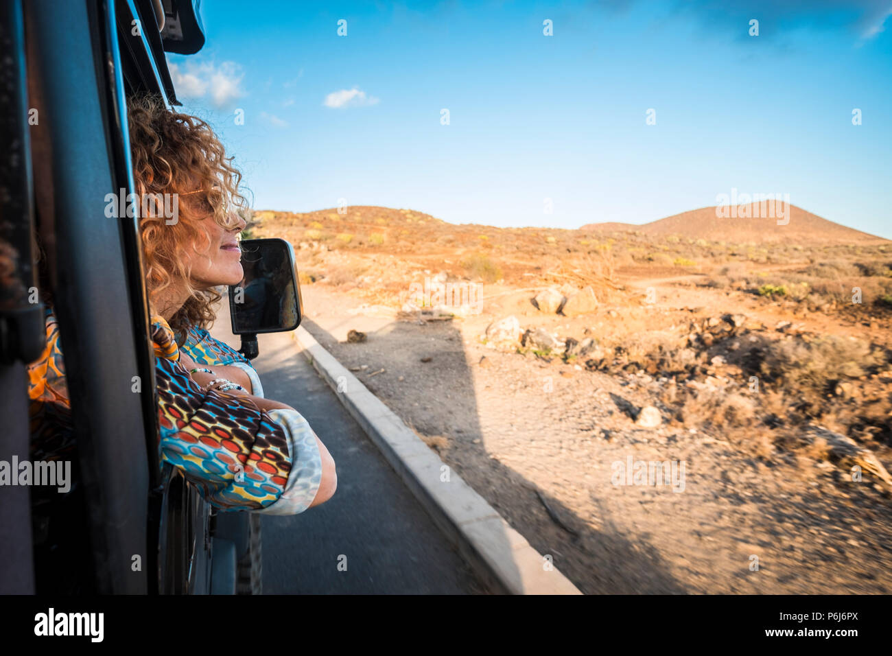 beautiful caucasian young woman traveling with an off road black car and looking outside the landscape. desert and mountains travel scenic place for n - Stock Image