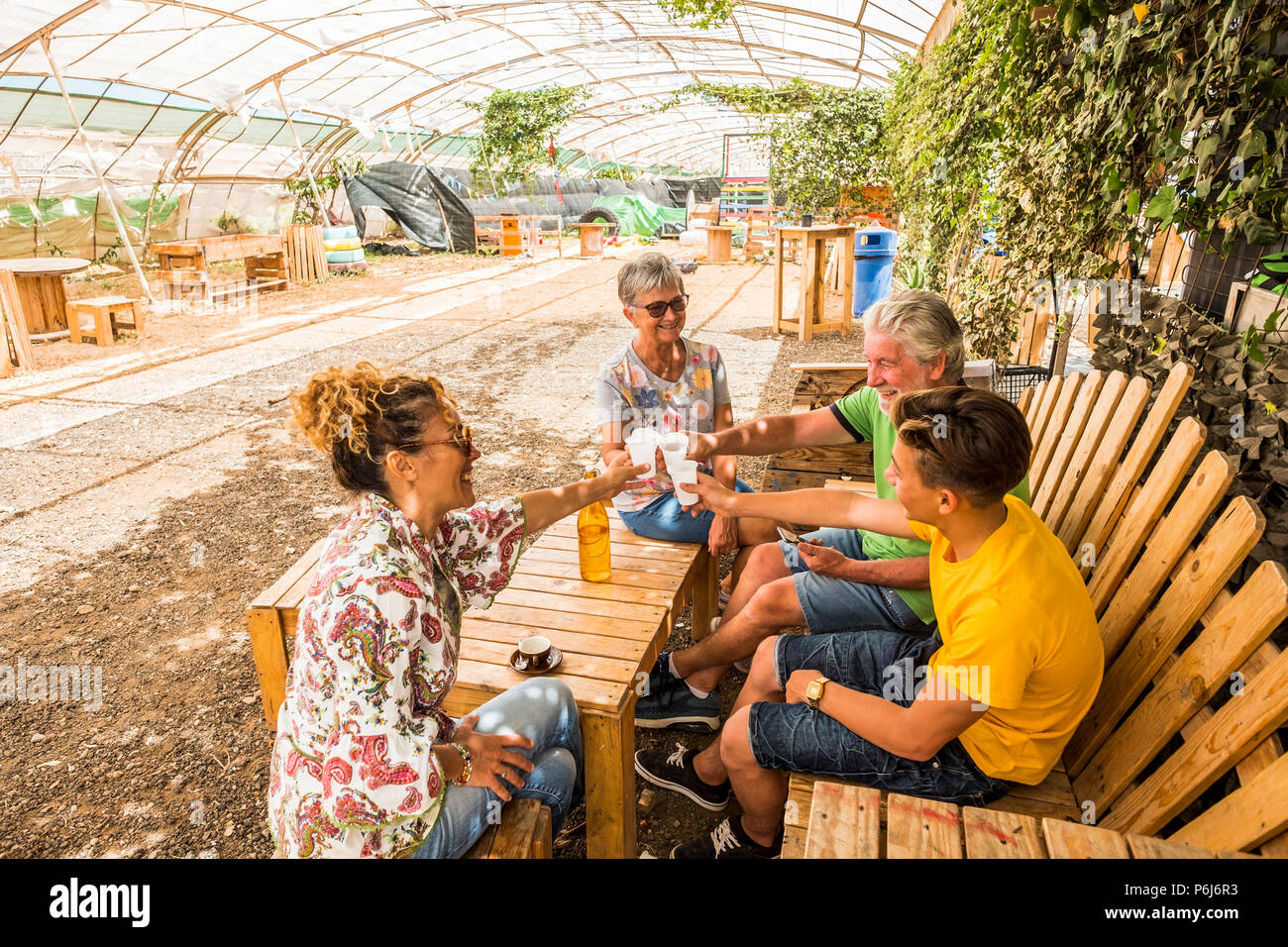 entire family from teenager to mother to grandfathers celebrate together in an outdoor bar restaurant in the nature. happiness all together with smile - Stock Image