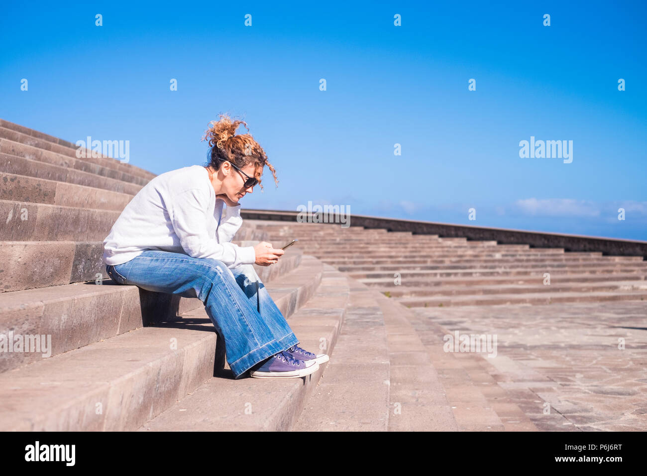 lonely middle age woman at work with a smartphone sitting on a long beautiful staris in urban contest. leisure with tehnology concept for modern lady  - Stock Image
