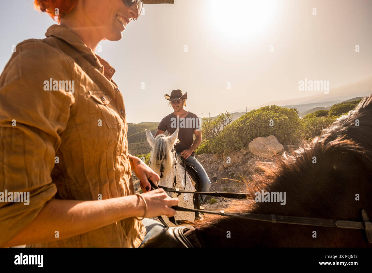 nice caucasian cowboys couple ride horses in wind ladscape scenic place. woman and man together have fun with horse therapy and enjoy the sunset. smil Stock Photo