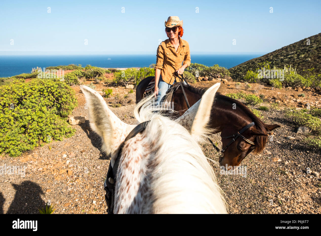 smiling beautiful red hair lady young ride a horse. view from another rider and whit ehorse. leisure activity outdoor with fun in couple. horse therap - Stock Image