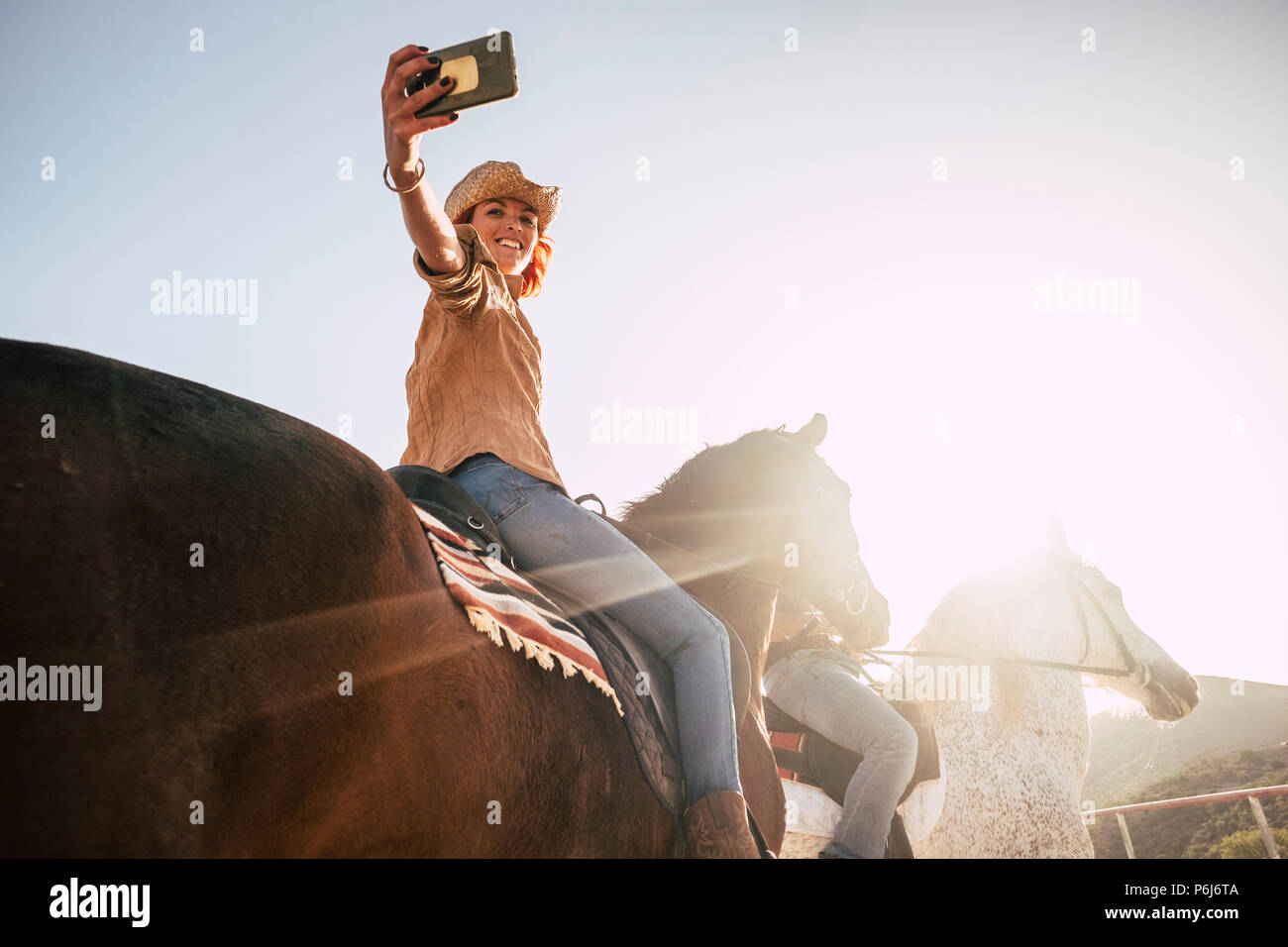 couple riding horses take a selfie with modern technology smartphone. cowboy lifestyle and smile woman. sunset time and backlight for outdoor leisure  - Stock Image