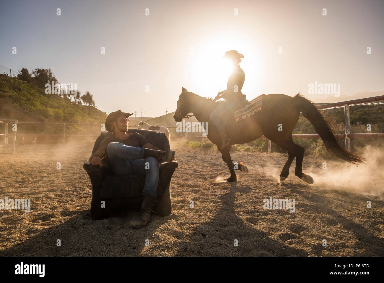 riders with horses in the golden sunset light. a man sitting on an old seat and a woman ride around him making dust. scenery image with windmills in b - Stock Image