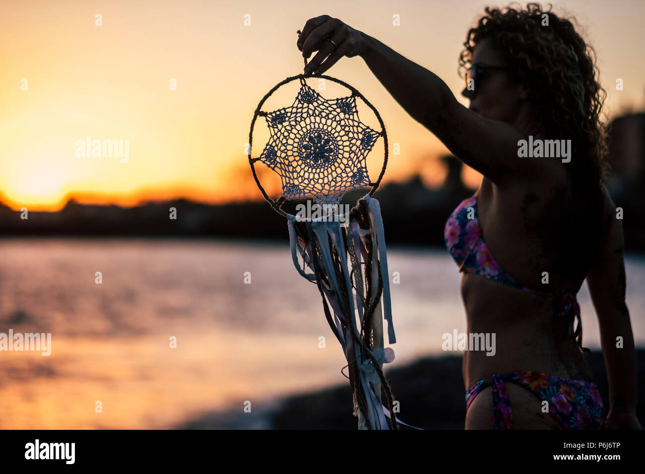 young beautiful woman take a dreamcatcher during the wonderful sunset at the beach in front of the ocean. feeling with the nature and healthy lifestyl Stock Photo
