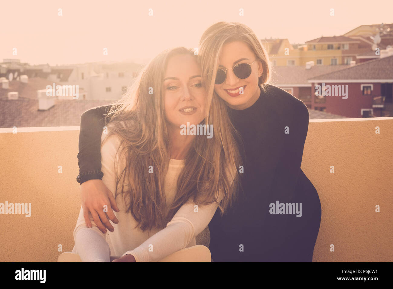 couple of two beautiful models females hugging outdoor on the rooftop terrace at home. sunset time and sunlight with backlight, elegance and beauty in - Stock Image