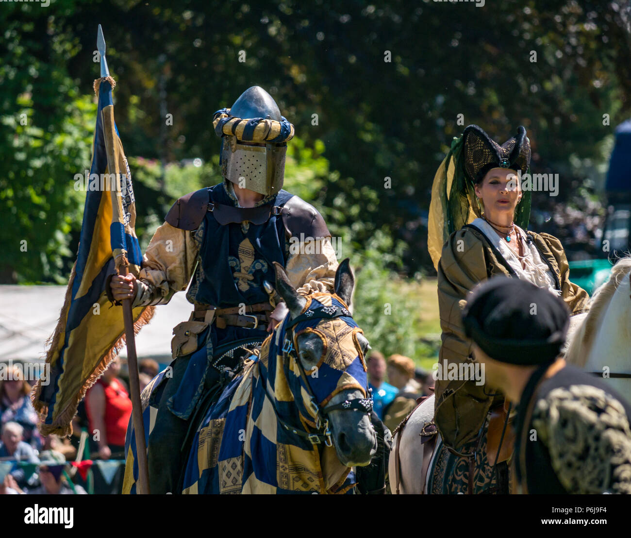 Jousting and Medieval Fair at Linlithgow Palace, Linlithgow, Scotland, United Kingdom, 30th June 2018. Historic Environment Scotland kick off their summer entertainment programme with a fabulous display of Medieval jousting in the grounds of the historic castle. The family fun day includes living history camps, medieval games, crafts, archery, and falconry. The jousting is performed by Les Amis D'Onno equine stunt team based in the Borders. Knight Sir Antoine Le Grand Chevalier D'Outremer, played by Antoine Ruault and Sue Zacharias on a white horse as a Medieval Lady - Stock Image