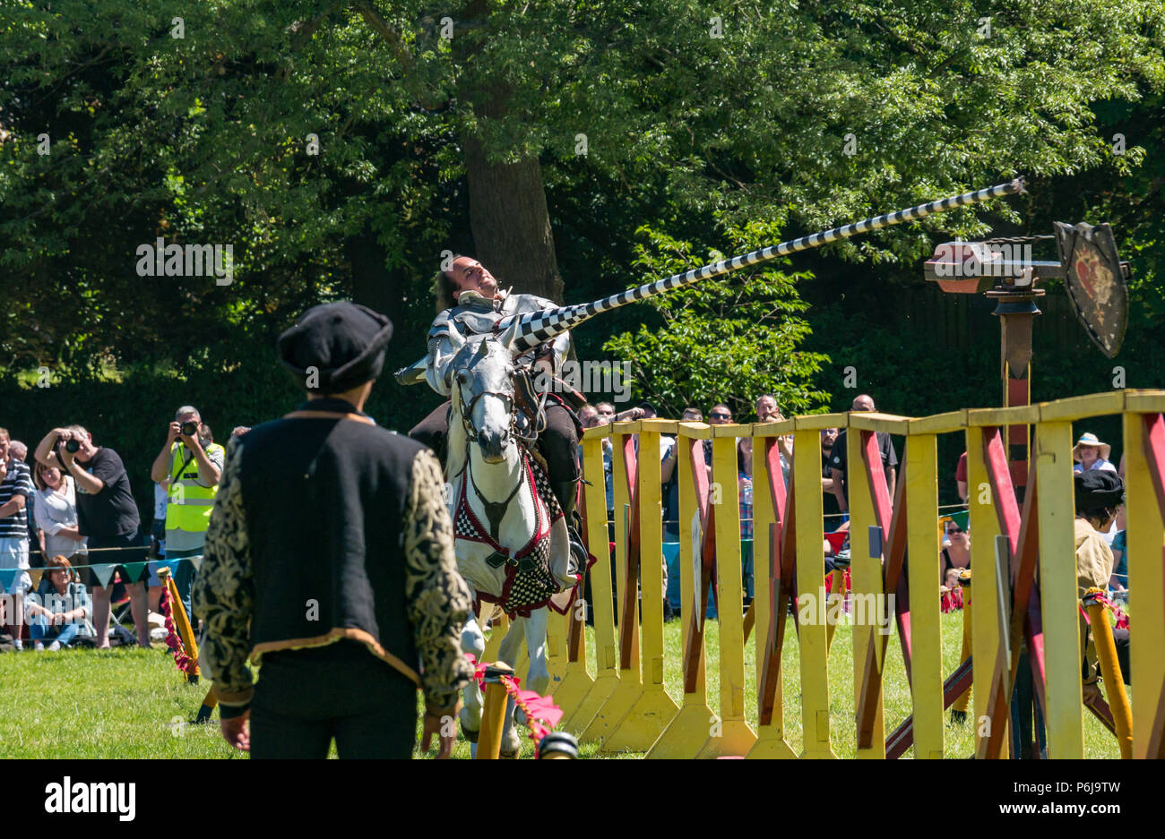 Jousting and Medieval Fair at Linlithgow Palace, Linlithgow, Scotland, United Kingdom, 30th June 2018. Historic Environment Scotland kick off their summer entertainment programme with a fabulous display of Medieval jousting in the grounds of the historic castle. The family fun day includes living history camps, medieval games, crafts, archery, and falconry. The jousting is performed by Les Amis D'Onno equine stunt team based in the Borders. Knight Sir Checkmate Fitzpercy, played by Jacob Martin, riding his horse with a lance - Stock Image