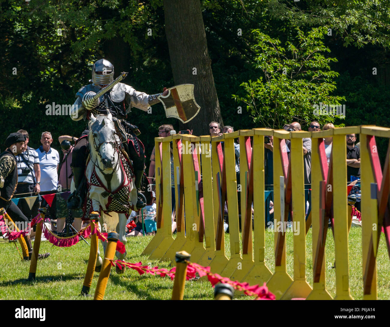 Jousting and Medieval Fair at Linlithgow Palace, Linlithgow, Scotland, United Kingdom, 30th June 2018. Historic Environment Scotland kick off their summer entertainment programme with a fabulous display of Medieval jousting in the grounds of the historic castle. The family fun day includes living history camps, medieval games, crafts, archery, and falconry. The jousting is performed by Les Amis D'Onno equine stunt team based in the Borders. Knight Sir Checkmate Fitzpercy, played by Jacob Martin, jousts riding his horse with a lance - Stock Image