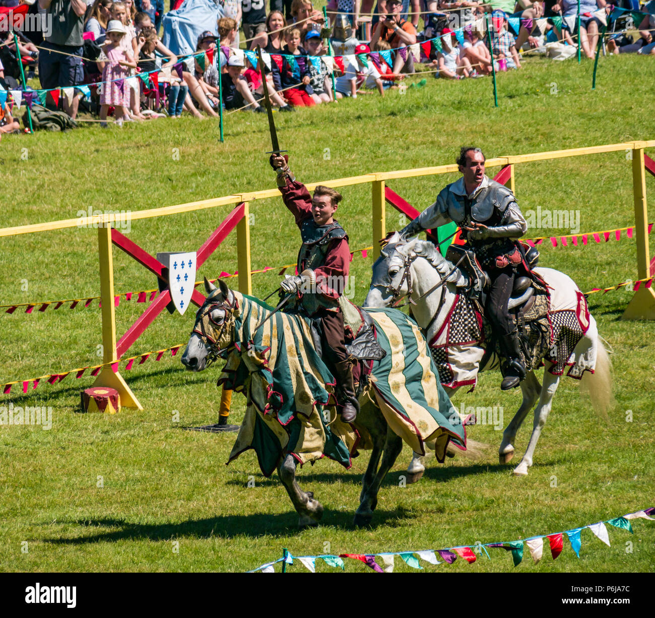 Jousting and Medieval Fair at Linlithgow Palace, Linlithgow, Scotland, United Kingdom, 30th June 2018. Historic Environment Scotland kick off their summer entertainment programme with a fabulous display of Medieval jousting in the grounds of the historic castle. The family fun day includes living history camps, medieval games, crafts, archery, and falconry. The jousting is performed by Les Amis D'Onno equine stunt team based in the Borders. Knight Sir Checkmate Fitzpercy, played by Jacob Martin, Knight Sir Archibald Douglas, played by  Bob Emmerson, ride their horses - Stock Image