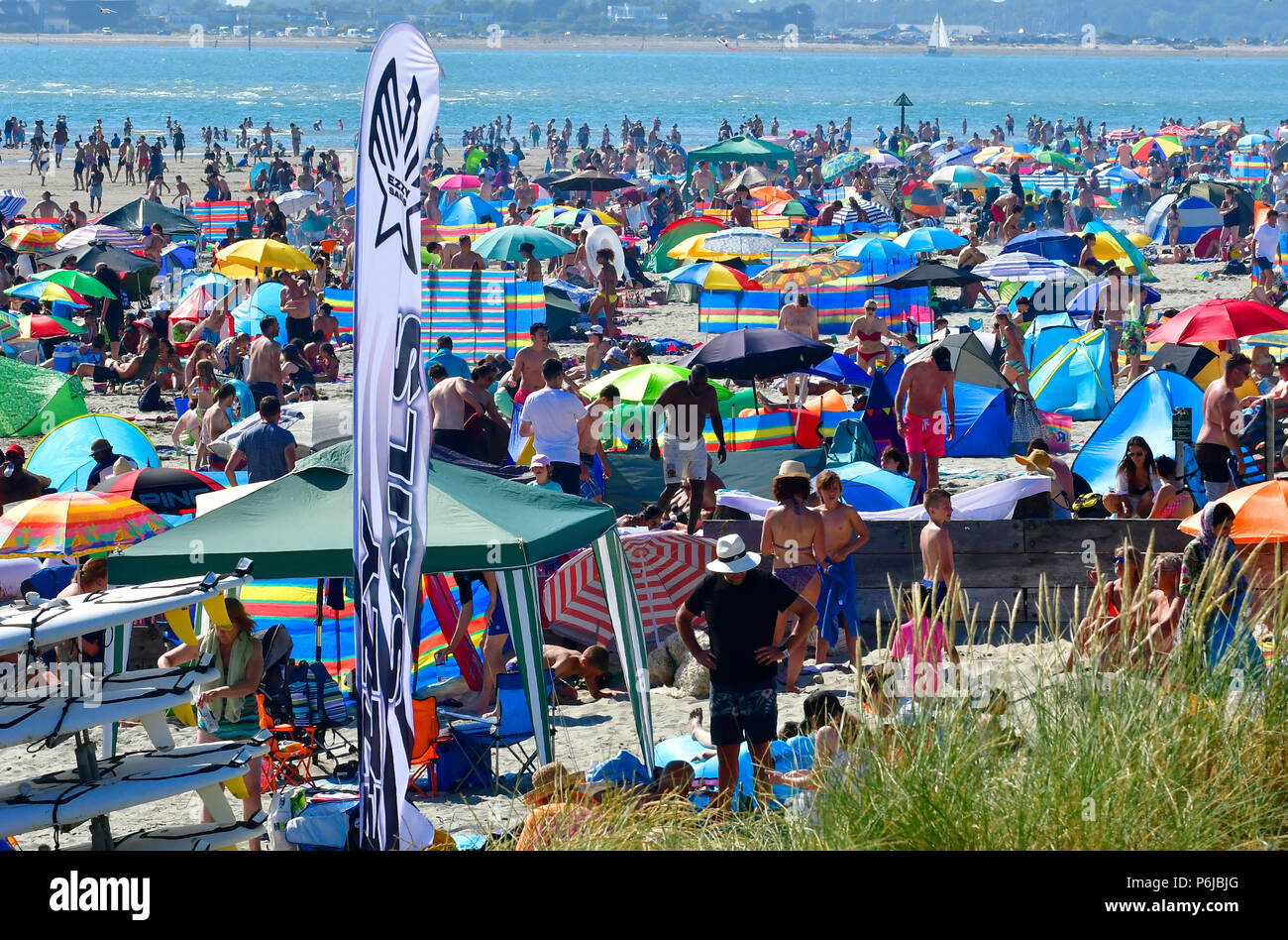 West Wittering beach   on a hot summers weekend in july ,packed with day trippers enjoying the heatwave and swimming in the sparkling water on its Blue Flag beach - Stock Image