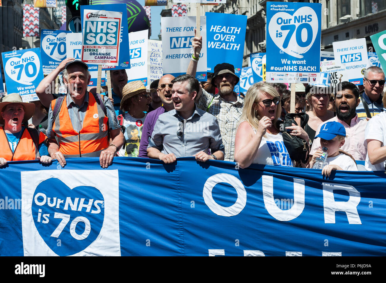 London, UK. 30th June, 2018. Shadow Health Secretary Jonathan Ashworth (C) joined thousands of demonstrators taking part in a march followed by a rally outside Downing Street in central London to celebrate the 70th anniversary of the National Health Service. Protesters call for an end to austerity policies which lead to underfunding and staff shortages in the NHS, and demand that it remains publicly owned and accessible to everyone. Credit: Wiktor Szymanowicz/Alamy Live News - Stock Image