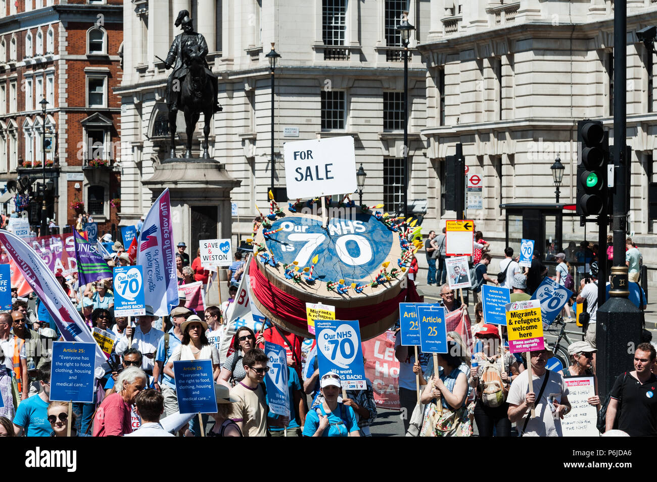London, UK. 30th June, 2018. Thousands of demonstrators take part in a march followed by a rally outside Downing Street in central London to celebrate the 70th anniversary of the National Health Service. Protesters call for an end to austerity policies which lead to underfunding and staff shortages in the NHS, and demand that it remains publicly owned and accessible to everyone. Credit: Wiktor Szymanowicz/Alamy Live News - Stock Image