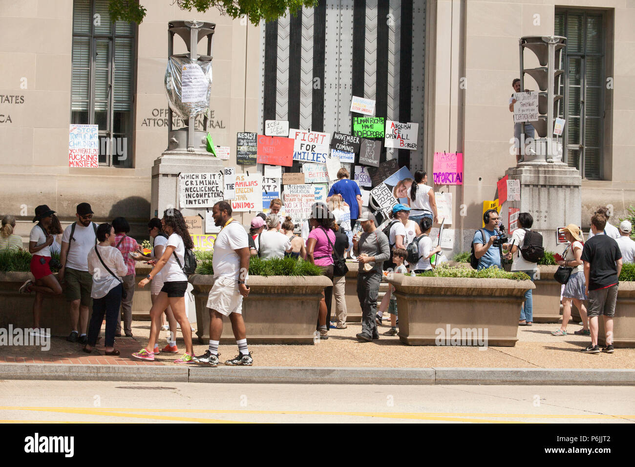 Washington DC, USA. 30th Jun, 2018. People attach protest signs to the doors of the Department of Justice during the Families Belong Together Rally in Washington, D.C., June 30, 2018. Credit: Robert Meyers/Alamy Live News Stock Photo