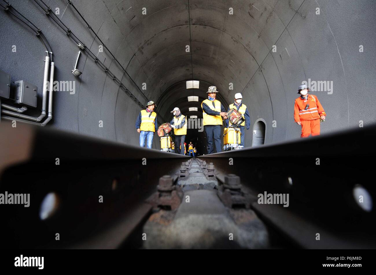 Beijing, Qinghai-Tibet Railway in northwest China's Qinghai Province. 27th June, 2018. Maintenance workers check the tracks at the Xinguanjiao Tunnel, the world's longest plateau rail tunnel, along the Qinghai-Tibet Railway in northwest China's Qinghai Province, June 27, 2018. Credit: Hou Deqiang/Xinhua/Alamy Live News - Stock Image