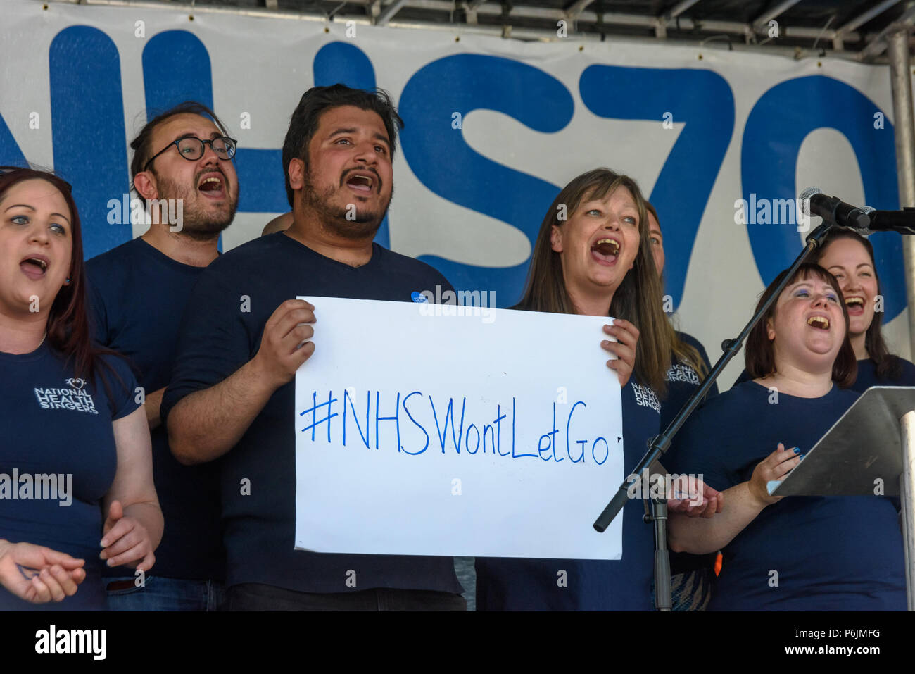 June 30, 2018 - London, UK. 30th June 2018. The NHS singers begin the rally near Downing St to celebrate 70 years of the NHS, and to support its dedicated workers in demanding a publicly owned NHS that is free for all with proper funding and proper staffing and providing a world class services for every community. The protest, organised by the the People's Assembly, Health Campaigns Together, Trades Union Congress, Unison, Unite, GMB, British Medical Association, Royal College of Nursing, Royal College of Midwives, CSP, BDA, and SoR was to defend the NHS against the increasing attacks and pr - Stock Image