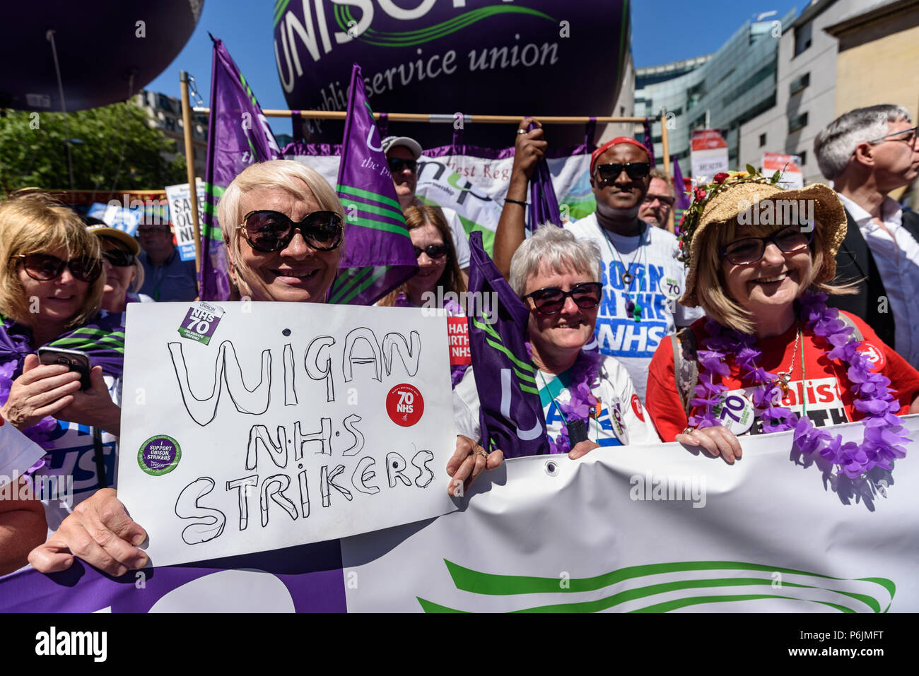 June 30, 2018 - London, UK. 30th June 2018. Wigan NHS strikers were near the front of the march as thousands marched through London from the BBC to a rally near Downing St to celebrate 70 years of the NHS, and to support its dedicated workers in demanding a publicly owned NHS that is free for all with proper funding and proper staffing and providing a world class services for every community. The protest, organised by the the People's Assembly, Health Campaigns Together, Trades Union Congress, Unison, Unite, GMB, British Medical Association, Royal College of Nursing, Royal College of Midwive - Stock Image