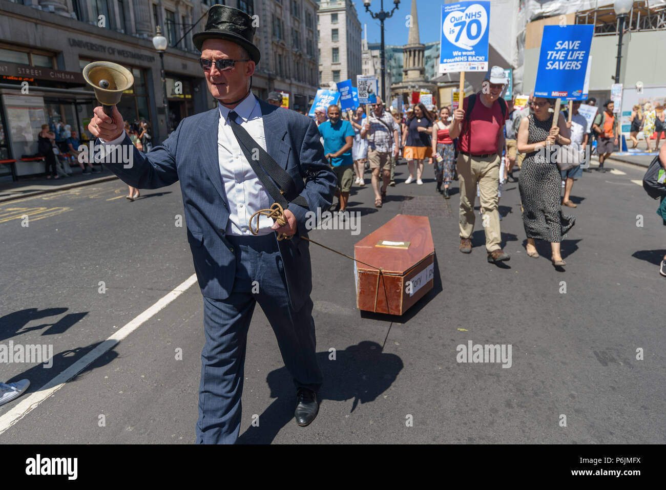 June 30, 2018 - London, UK. 30th June 2018. A man in a black top hat and tie rings a bell as he drags a coffin representing the NHS on the march through London from the BBC to a rally near Downing St to celebrate 70 years of the NHS, and to support its dedicated workers in demanding a publicly owned NHS that is free for all with proper funding and proper staffing and providing a world class services for every community. The protest, organised by the the People's Assembly, Health Campaigns Together, Trades Union Congress, Unison, Unite, GMB, British Medical Association, Royal College of Nursi - Stock Image