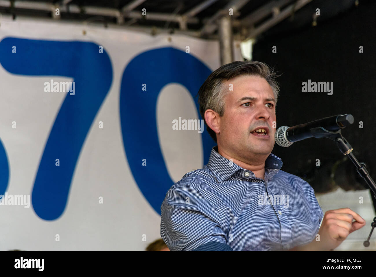June 30, 2018 - London, UK. 30th June 2018. Shadow Health Minister Jonathan Ashworth MP speaks at the rally near Downing St to celebrate 70 years of the NHS, and to support its dedicated workers in demanding a publicly owned NHS that is free for all with proper funding and proper staffing and providing a world class services for every community. The protest, organised by the the People's Assembly, Health Campaigns Together, Trades Union Congress, Unison, Unite, GMB, British Medical Association, Royal College of Nursing, Royal College of Midwives, CSP, BDA, and SoR was to defend the NHS again - Stock Image