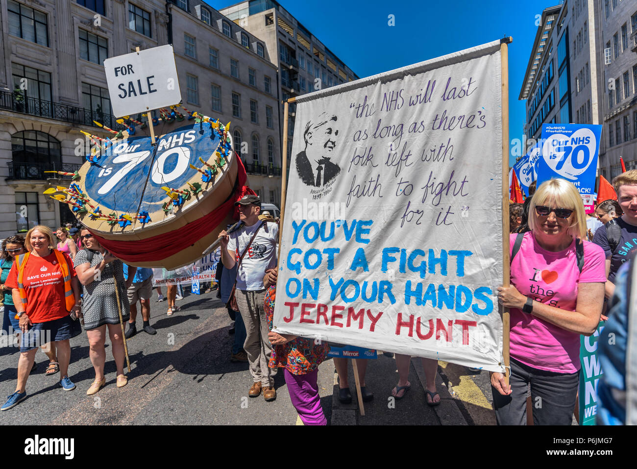 June 30, 2018 - London, UK. 30th June 2018. A huge birthday cake celebrating the NHS at 70 with the message 'FOR SALE' next to a banner with a quotation attributed to Aneurin Bevan as thousands wait to march through London from the BBC to a rally near Downing St to celebrate 70 years of the NHS, and to support its dedicated workers in demanding a publicly owned NHS that is free for all with proper funding and proper staffing and providing a world class services for every community. The protest, organised by the the People's Assembly, Health Campaigns Together, Trades Union Congress, Unison, - Stock Image