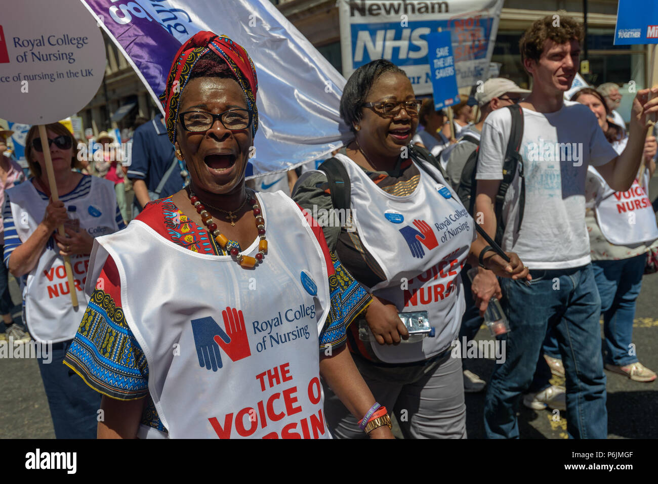 June 30, 2018 - London, UK. 30th June 2018. Royal College of Nursing (RCN) President Cecilia Anim (left) with other nurses on the march through London from the BBC to a rally near Downing St to celebrate 70 years of the NHS, and to support its dedicated workers in demanding a publicly owned NHS that is free for all with proper funding and proper staffing and providing a world class services for every community. The protest, organised by the the People's Assembly, Health Campaigns Together, Trades Union Congress, Unison, Unite, GMB, British Medical Association, Royal College of Nursing, Royal - Stock Image