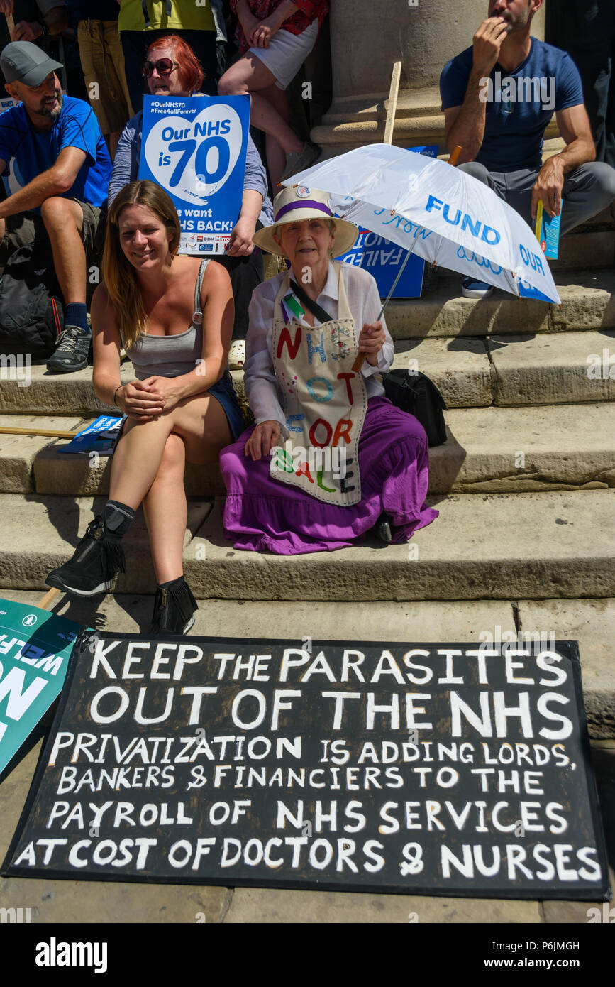 June 30, 2018 - London, UK. 30th June 2018. People sit on the steps as they wait to march through London from the BBC to a rally near Downing St to celebrate 70 years of the NHS, and to support its dedicated workers in demanding a publicly owned NHS that is free for all with proper funding and proper staffing and providing a world class services for every community. The protest, organised by the the People's Assembly, Health Campaigns Together, Trades Union Congress, Unison, Unite, GMB, British Medical Association, Royal College of Nursing, Royal College of Midwives, CSP, BDA, and SoR was to - Stock Image