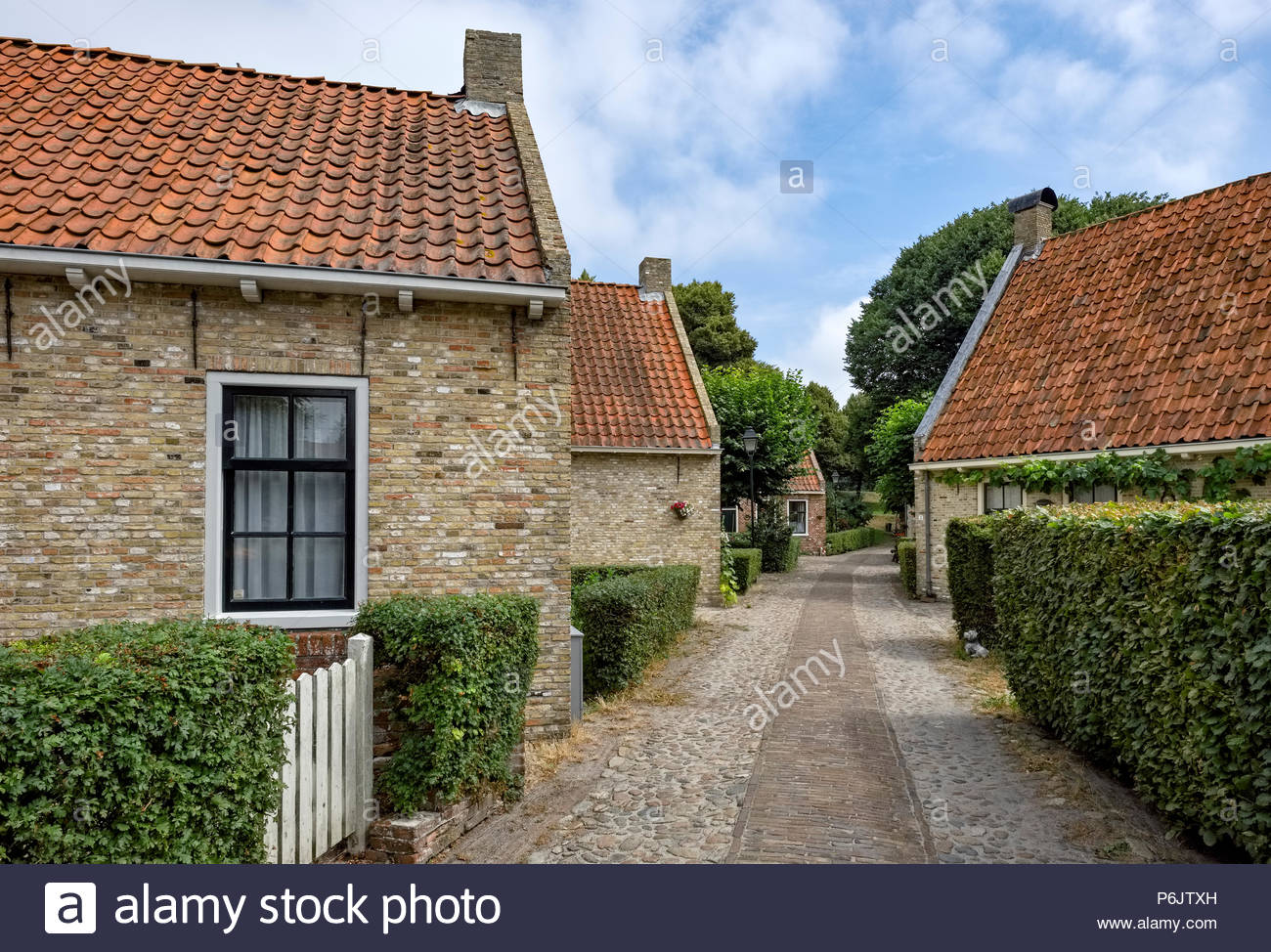 A cobblestone path runs between brick houses in the village at Vesting Bourtange, the star-shaped fortress in Groningen Province, The Netherlands. - Stock Image