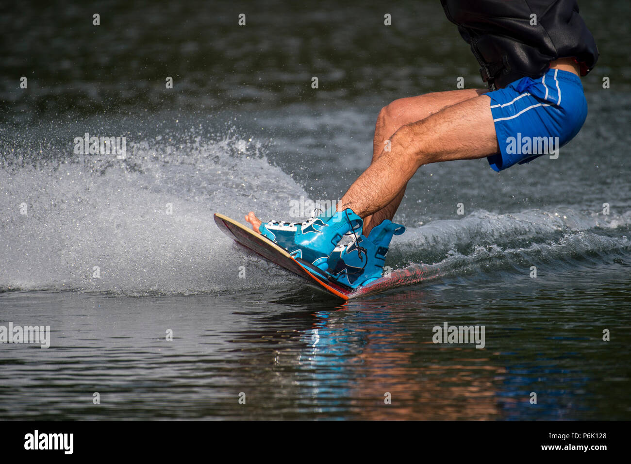 male wakeboarder rides on lake in wakeboard splashes of water - Stock Image