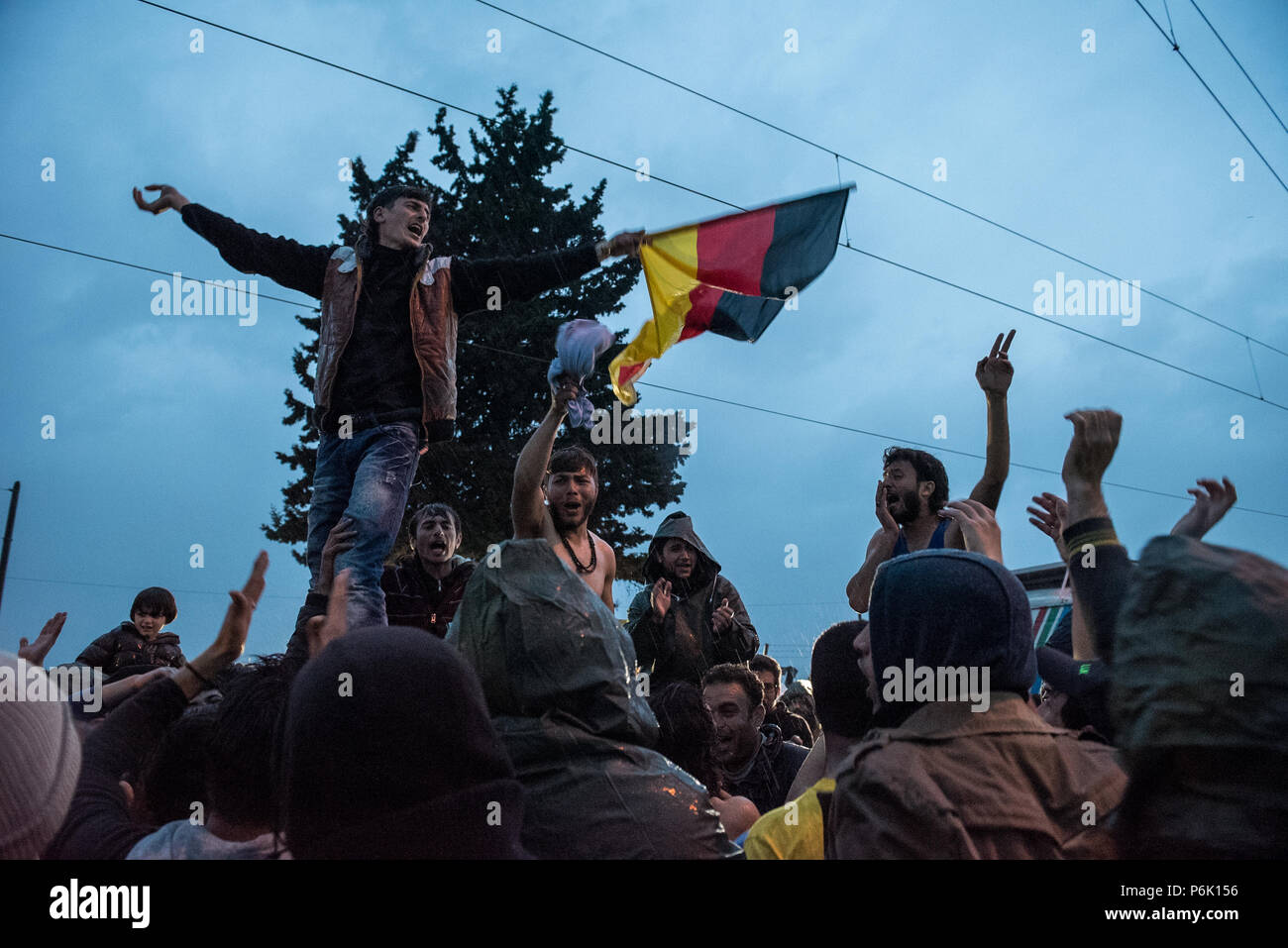Refugees wave a German flag as they call for borders to be open and celebrated the support received from German Chancellor Angela Merkel at the makesh - Stock Image