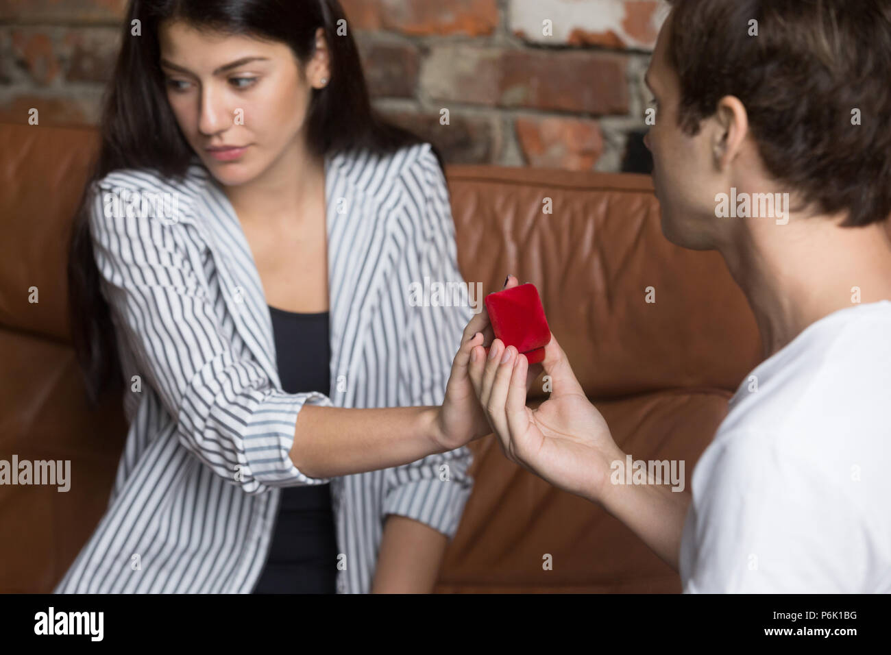 Unhappy girl refusing to marriage proposal of boyfriend - Stock Image