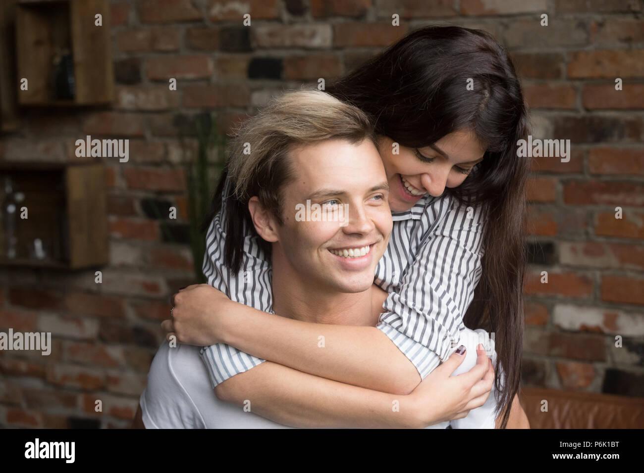 Happy girlfriend piggyback smiling boyfriend having fun at home - Stock Image