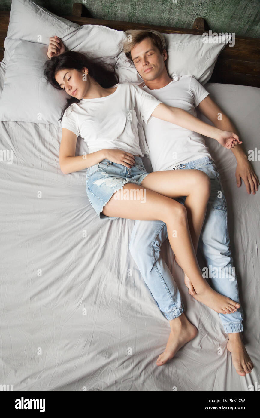 Young girlfriend fell asleep on top of boyfriend in bed - Stock Image