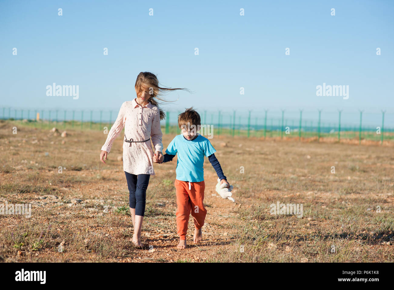 two kids migrants walking in desert shoeless with plush toy along state border fencing - Stock Image