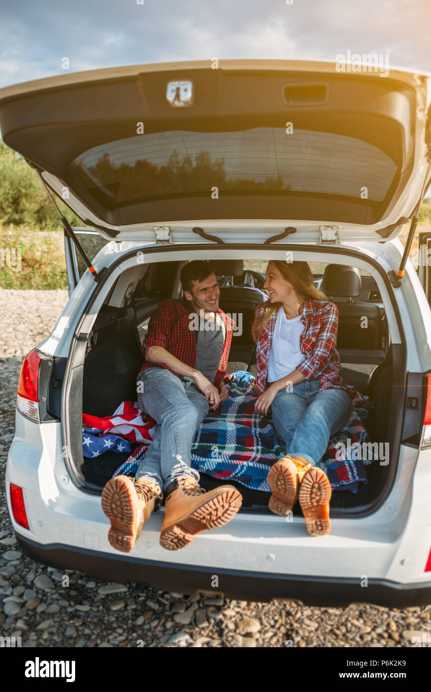 Happy traveler couple sitting in car open trunk and communicate at sunrise - Stock Image