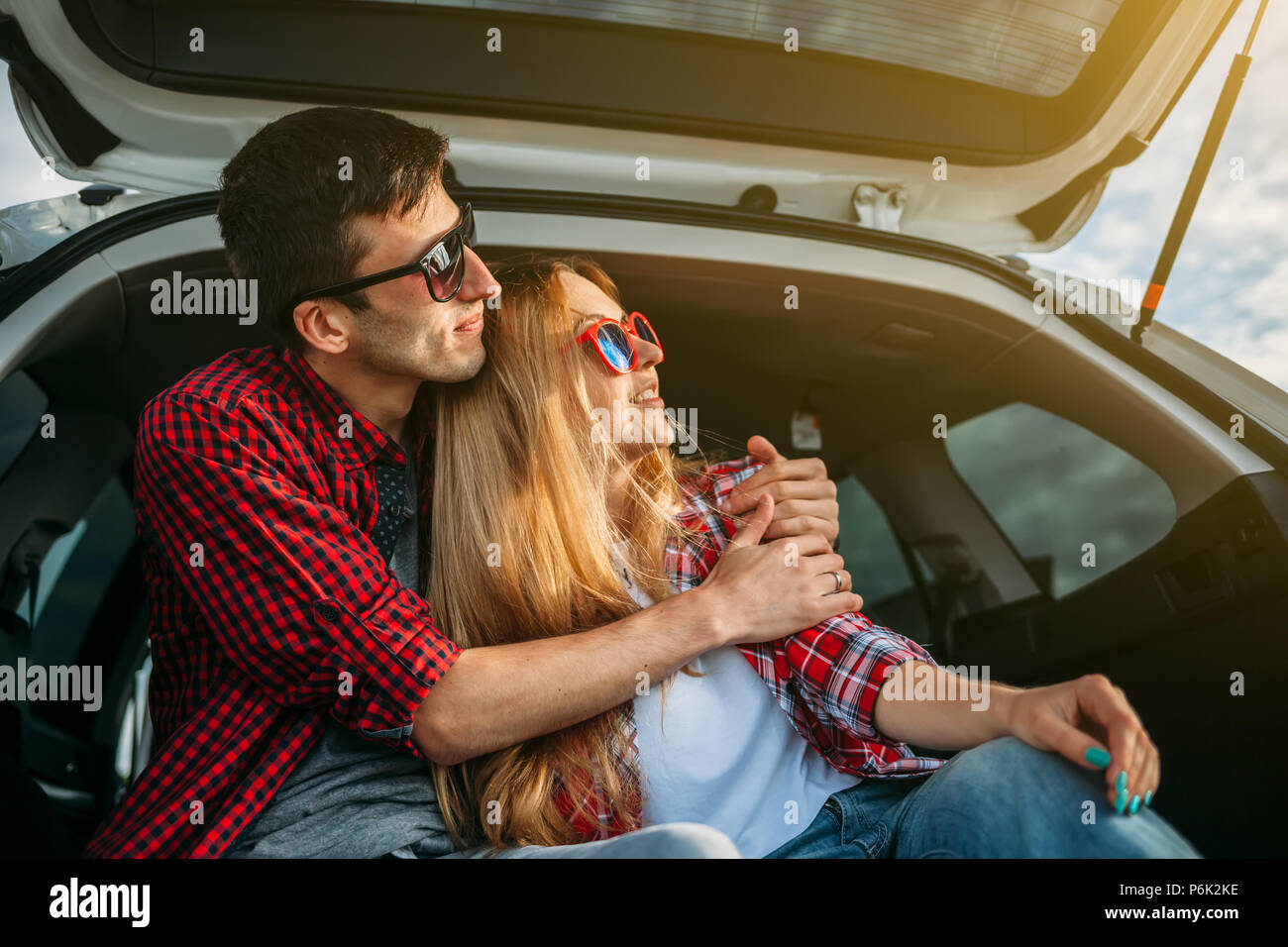 Happy traveler couple sitting in car open trunk and watch the sunrise - Stock Image