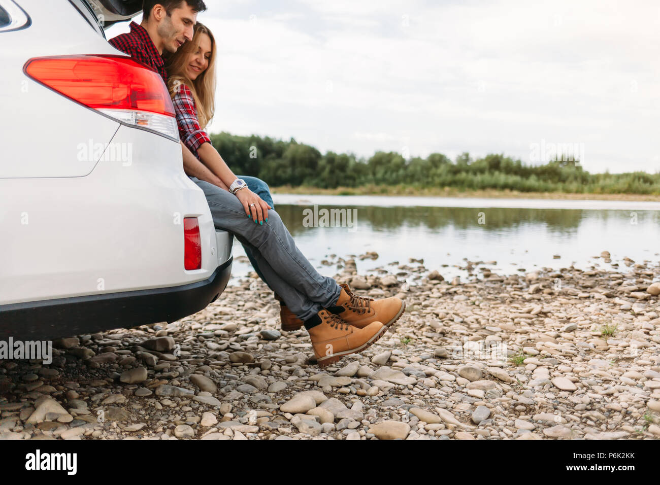 Happy traveler couple sitting in car open trunk and look at the river - Stock Image