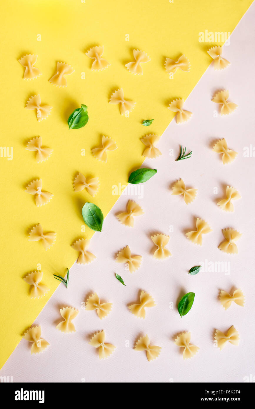 Farfalle Pasta on pink pastel and yellow background, top view, flat lay. Pattern uncooked farfalle pasta with herbs basil and rosemary. - Stock Image
