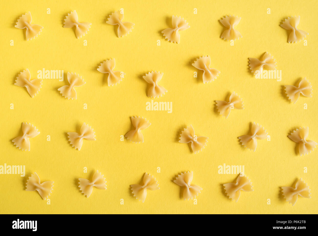 Farfalle Pasta on yellow background, top view, flat lay. - Stock Image