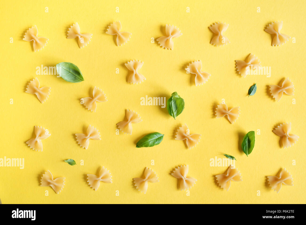 Farfalle Pasta on yellow background, top view, flat lay. Pattern uncooked farfalle pasta with basil leaves. - Stock Image