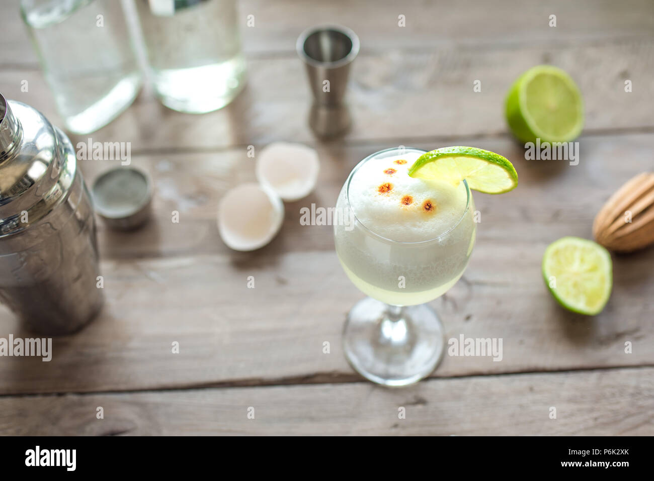 Pisco Sour Cocktail. Peruvian, Mexican, Chilean traditional drink pisco sour liqueur with  lime and egg and bar equipment for making. - Stock Image